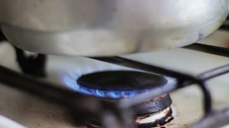 fogão : Old, dirty white gas stove which burns natural gas blue. Close-up, Man ignites ring stove. Natural Gas Inflammation In Stove Burger. Reheating the kettle on the stove.