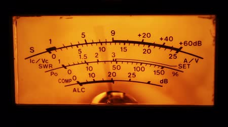 véu : Dial indicator and signal level meter. Dial gauge modes transceiver radio stations close-up. Bright orange, yellow lights. Analog signal indicator.