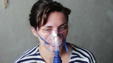 oksijen : The girl with the disease asthma, wears a mask for inhalation and the process of lungs inhalation using a nebuliser. She exhales steam from the mouth and inhale the vapors medications.