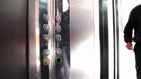 açoitado : People inside the elevator, press the button with a choice of floor and ride in it. The elevator door opens and closes. Lift modern, clean and glossy.
