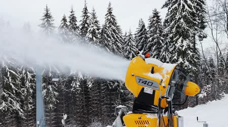 water cannon : Yellow snow cannon stands on a snowy mountain in the winter and works by producing a column of snow on the background of beautiful mountains, snow-covered pine trees, and the ski slopes. Stock Footage