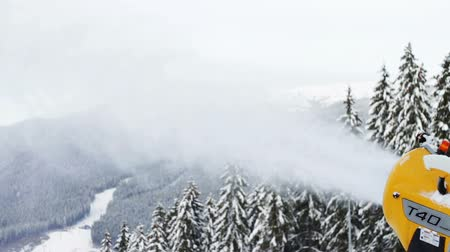 holiday makers : Yellow snow cannon stands on a snowy mountain in the winter and works by producing a column of snow on the background of beautiful mountains, snow-covered pine trees, and the ski slopes. Stock Footage