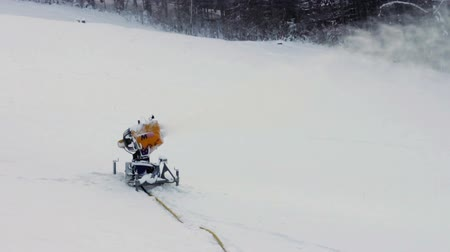 water cannon : Yellow snow cannons stand on a snowy mountain in the winter and work by producing a column of snow on the background of beautiful mountains, snow-covered pine trees, and the ski slopes. View from the top of the ski lifts in motion.
