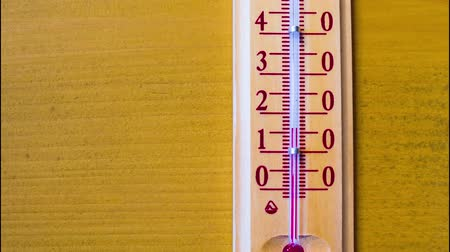 temp : Red mercury showing temperature of the air is rapidly growing up in a wooden thermometer, which weighs on the wooden wall of a house. Timelapse Stock Footage