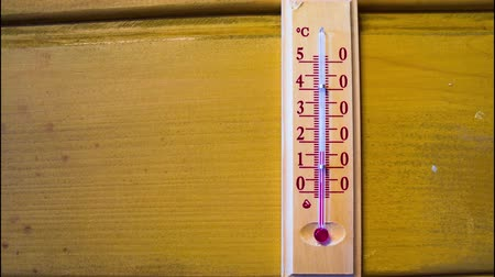 mercúrio : Red mercury showing temperature of the air is rapidly growing up in a wooden thermometer, which weighs on the wooden wall of a house. Timelapse Vídeos