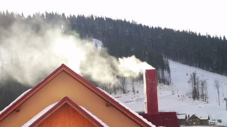 superb : The smoke from the chimney of the restaurant on the background of wooden houses Bukovel ski resort. Smoking pipe on a snowy roof in a cold winter day. Stock Footage