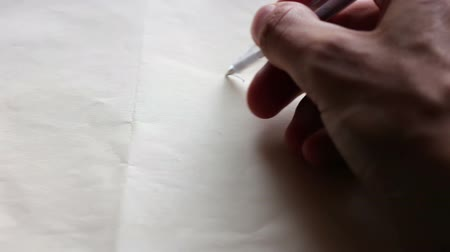 inspiração : A man draws a heart pen on white paper.