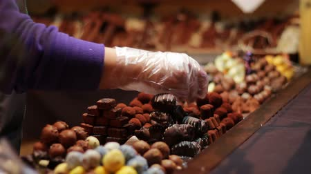 cukrozott : On a Christmas fair, people buy nuts, chocolate, candies, and other sweets and cookies. Seller sells chocolate Christmas market stalls in the New Year in the winter. Stock mozgókép