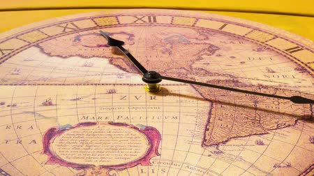 clock hands : Analog Clock with the image of the world map hanging on the wall and work. Minute and hour hands run along the rim of the dial. Timelapse.