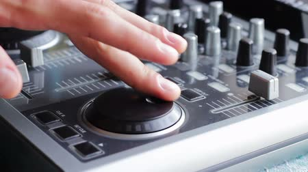 tokmak : DJ working with an analog audio mixer. Fingers hand man to raise and lower the fader, Spin a Jog Wheel, turn the handle and insert the plug into the socket on the mixer.