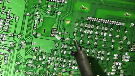 solder : Close-up of male radio engineer working with a soldering iron in his hand, which is the green braze mounting the circuit board with radio components in a laboratory.