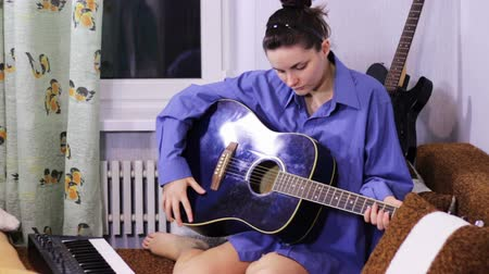 acoustical : Young beautiful girl learning to play the guitar at home.