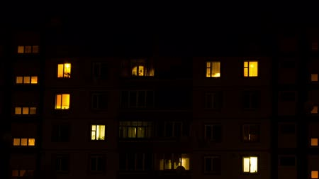 apartamentos : Time lapse of multistorey building with changing window lighting at night.