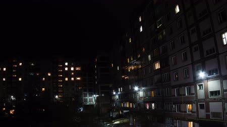 daireler : Time lapse of multistorey building with changing window lighting at night.