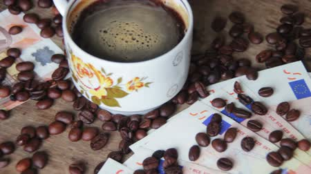 xícara de café : Coffee Beans, Coffee Cup and Euro on a Wooden Table