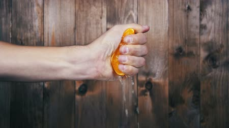 orange background : Squeeze the Juice from the Orange by Hand. Slow Motion
