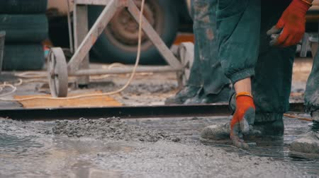 manivela : Pouring, Laying Concrete at the Construction Site using Buckets of Cement. Slow Motion Stok Video