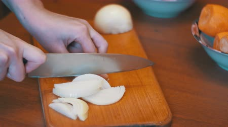 chop up : Woman Hands with Knife Cut Onion on Kitchen Board in Home Kitchen