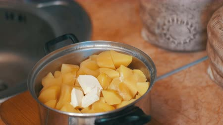 short clip : Piece of Butter Falls into the Potatoes in a Saucepan on the Home Kitchen