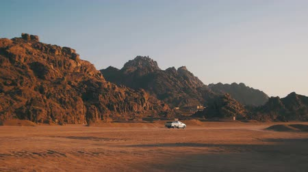 aridez : Pickup truck moves Through the Desert in Egypt, on Sand and Mountains Background