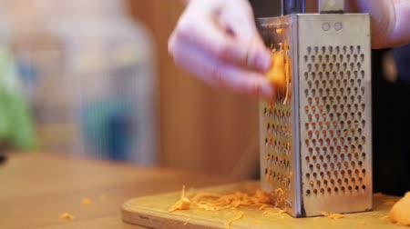 slicer : Woman Hands Rubbing Carrots on Grater in a Home Kitchen. Slow Motion