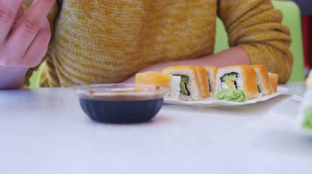 plating food : Woman with Chopsticks Eating Sushi from a Plate in a Japanese Restaurant. Dolly Shot Stock Footage
