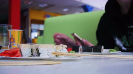 plating food : Man uses a Mobile Phone in a Japanese Sushi Restaurant Stock Footage