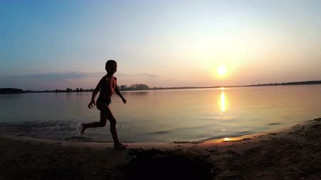 jump away : Silhouette of Happy Child Running Along the Beach at Sunset. Slow Motion