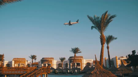 řev : Large Passenger Plane Flying in the Sky over Hotels in Egypt