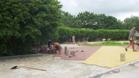 paving blocks : The Building Process, Repairing Sidewalk. Worker Laying Stone Paving in a city Park Stock Footage