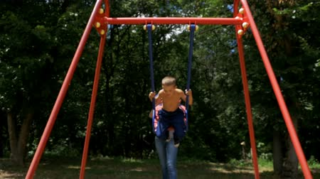 lökés : Mother Ride her Little Son on a Street Swing at Playground in Slow Motion