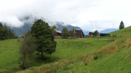 hayloft : Landscape view of an Old Wooden House Alm on a Background of Alpine Mountains and Clouds