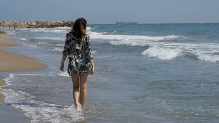 protects : Young Girl Walks along the Beach of the Sea Coast in Slow Motion