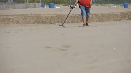 buried treasure : Man with a Metal Detector Walks along a Sandy Beach on the Seashore. Slow Motion