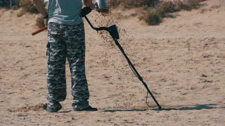 buried treasure : Man with a Metal Detector Walks along a Sandy Beach on the Seashore Stock Footage