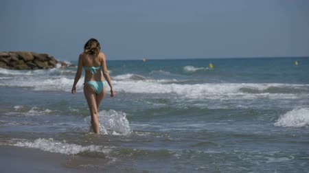 protects : Girl in bathing suit runs along the sea shore at the beach in Slow Motion Stock Footage