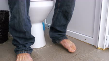 sanitário : The Legs of a Man Sitting on the Toilet