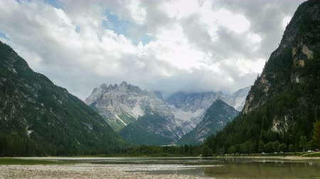 alpi : Clouds are Moving over the Peaks of the Alpine Mountains and a mountain lake. Time Lapse