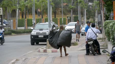 jobless : Asian man with large garbage bags walks along the sidewalk in slow motion. Thailand. Pattaya