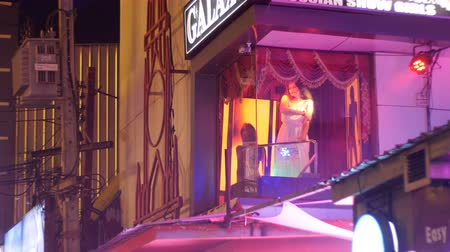 стриппер : Stripper girl spinning on a pole on the balcony. Walking Street in Pattaya at night. Thailand.