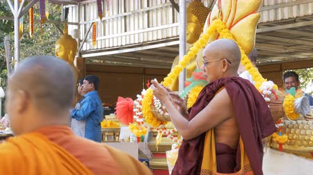 protestor : The monk uses mobile phone with a touchscreen in the temple of golden Buddha. Thailand