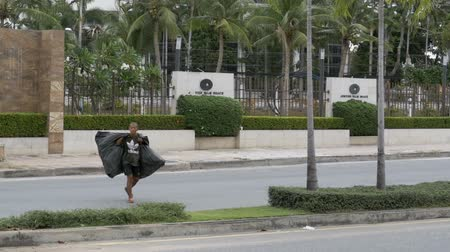 ghetto streets : Asian man with a large trash bags crossing the street in slow motion. Thailand, Pattaya. Stock Footage