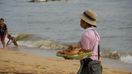 market vendor : Asian vendor woman carries tropical food sales on the beach. Pattaya, Thailand Stock Footage