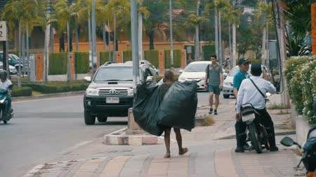 jobless : Asian man with large trash bags walks along the sidewalk in slow motion. Thailand. Pattaya