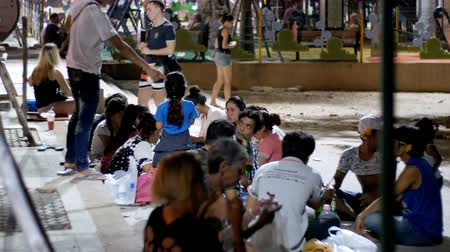 cena urbana : Asian people sitting on sidewalk eat food are in the evening near the sea on the embankment under palm trees