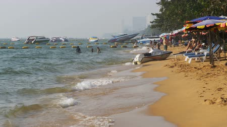 иностранец : Coastline of the beach. People bathe in the sea, water rides, wave beat on the sandy shore. Thailand. Pattaya.