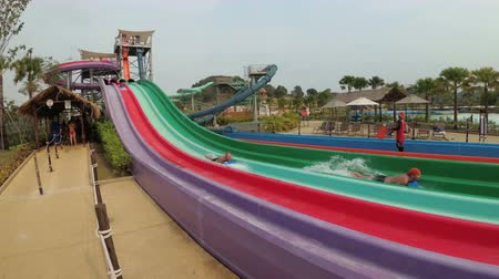 aqua park : People descend from the colorful water slides in the Aqua Park of the Ramayana. Slow Motion