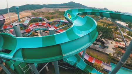 aqua park : A view from above on people descending on an inflatable circle from a water slide.