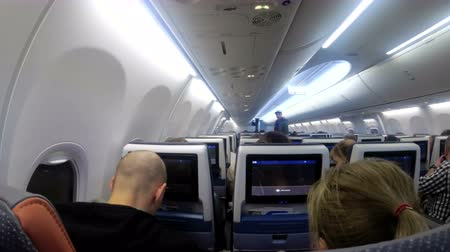 attendant : The passenger cabin with people of the airplane during the flight