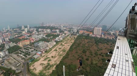 çatı : Jump from the Pattaya City Tower. Man goes down the cable from the roof. Thailand Stok Video